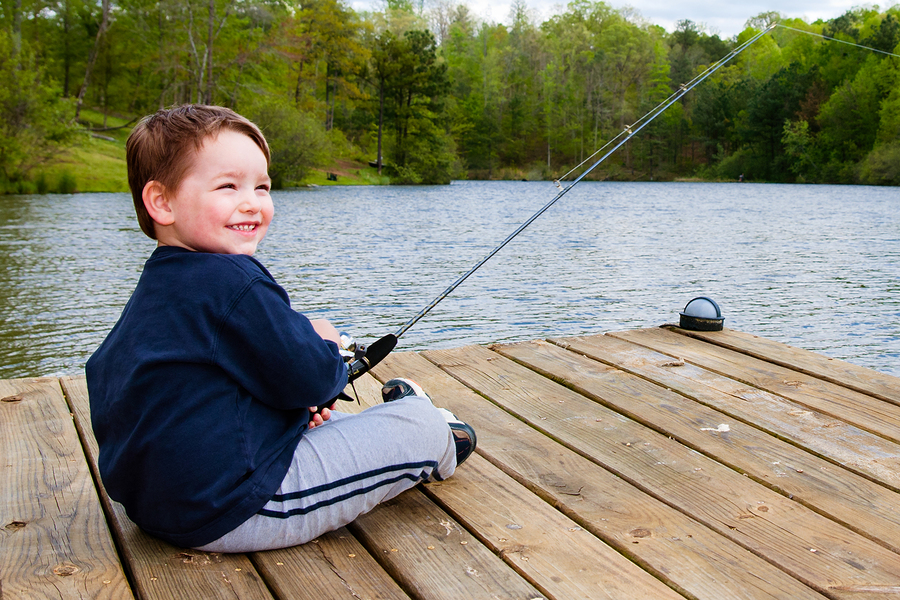 Bigstock Boy Smiles While Fishing From 18537422
