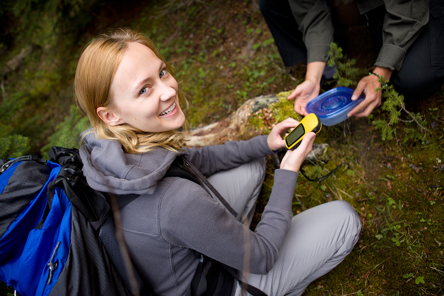 A young woman finding a geocache in the forest